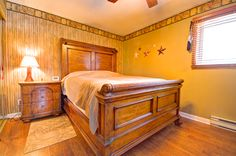 The master bedroom is warm, with golden brown paint and a faux-bamboo wall.  #Orangeville #OrangevilleOntario #OrangevilleRealEstate