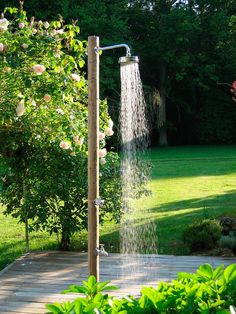 A Pilotis outdoor shower made of northern pine logs has a tap to turn on for a foot wash and a faucet to connect a watering hose; for information and pricing, see Douches de Jardins