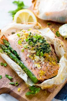 Opened parchment paper pouch with cooked salmon and asparagus