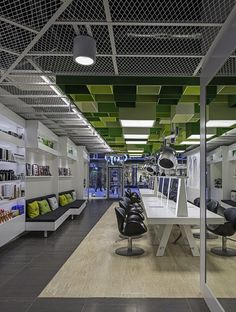 Green boxes pattern the ceiling of Clip Drop In hair salon by Sweco Architects.