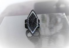 Bague élégante en perles Miyuki delicas couleur noir brillant et argenté, tissée à la main en méthode peyote et brick stich (perle par perle). Fil de nylon japonais Miyuki, noir, ultra-résistant. Taille : de 48 à 53 mm. LIVRAISON OFFERTE. Envoyée dans un petit sac dorganza bleu
