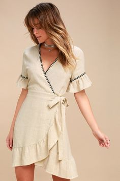 The Cyrus Beige Embroidered Wrap Dress is simple sophistication at its finest! Cute black stitched detail frames a surplice bodice and short flounce sleeves. Tying, ruffled wrap skirt (with hidden internal button) falls to a cute mini length.