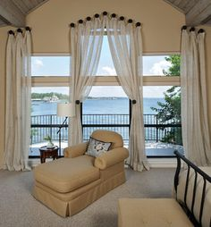 This is a Master Bedroom I would design for a beach or summer home. I love the light monochromatic color scheme incorporated in the paint colors, carpeting, draperies, furniture and bedding.  They contrast with the dark iron on bed and railings.  The drapery fabric is also light and transparent so not to block the ocean view.  It is open and light and comfortable brings the outdoors in.
