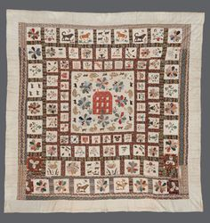 Red Manor House Apppliqué  Coverlet  Maker:     UNKNOWN Date:     1840 - 1860  Appliqué Frame Coverlet with a central motif of a Red Manor House surrounded by flowers and domestic/rural animals. The subsequent frames are divided into squares, with each one containing a different appliqué motif including flowers, plant pots, animals and houses. Each appliqué motif has decorative herringbone embroidery stitch to cover the edges and each square is surrounded by a printed cotton border.
