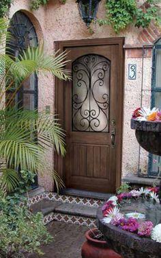 Entry doors, exterior doors Wrought iron and glass in a solid wood door