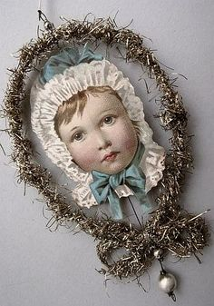 Antique paper scrap baby head in a tinsel frame christmas ornament.