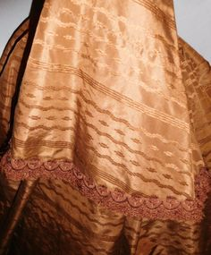 """1860s printed brown silk dress, pagoda sleeves w/ short cap trimmed with brown silk trim with fringe; piping at neck, armscyes & waist; bodice lined in cotton, front hook & eye closure, skirt fully lined in cotton; small area of light underarm discoloration mainly to lining, skirt waist band missing; minor fraying on hem binding; bust: 34""""; waist: 28"""", skirt length: 38-42""""; hem width: 146"""""""