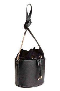 Mala saco detalhes em camurça: Pequena mala saco em pele sintética gravada com pormenores em camurça natural. Tem cordão de ajuste em cima, uma alça e três bolsos interiores, um deles com fecho éclair. Forrada. Medidas: 14x16 cm.