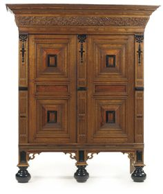 "A KAS. A DUTCH OAK, ROSEWOOD, WALNUT AND EBONIZED CUPBOARD, 19TH CENTURY. The rectangular moulded cornice above a tapering frieze carved with cherubs and flanked by scrolling acanthus, above a pair of doors with raised panels. 199 cm. high (78.33"") x 129 cm. (almost 51"") wide x 73 cm. (28.75"") deep."