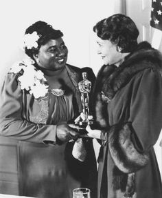 Hattie McDaniel receiving her Oscar for Gone With the Wind from Fay Bainter, February 1940. She was the first African-American to win an Academy Award.