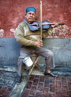 Lima, Peru: Man playing fiddle  Intriguing photography style...How'd they do that?