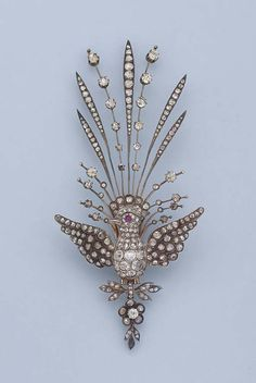 AN ANTIQUE DIAMOND AND RUBY BIRD BROOCH  The central old and rose-cut diamond bird with outstretched wings and ruby eye to the collet and line aigrette, suspending floral diamond pendant, circa 1890, 10.3 cm. high
