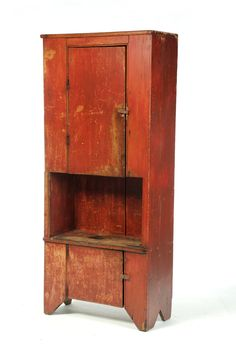 AMERICAN BUCKET BENCH-CUPBOARD. First half-19th century, pine. One piece cupboard with upper and lower plank doors and a central open section. Old red paint. Sold $3120