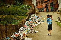 Boy with a baby in his hands walking down the road passing the piles of garbage Kathmandu Nepal Nepal Kathmandu, West Bengal, Street Photography, Mustang, Dolores Park, Walking, Hands, Baby, Travel
