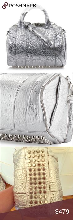 """100% Authentic Alexander Wang """"Rockie"""" Bag Silver ROCKIE PEBBLED LEATHER SLING BAG W/ LARGE MAIN COMPARTMENT AND GENEROUS ZIPPER OPENING. EXTERIOR HAS SILVER STUDDED BOTTOM AND HIDDEN POCKETS IN EXTERIOR SIDE GUSSET. ADJUSTABLE SHOULDER STRAP WITH SIGNATURE RHODIUM DOGCLIP AND TWO TOP HANDLES. POLYESTER LINED INTERIOR HAS ZIP POCKET WITH ALEXANDER WANG LOGO PATCH AND PHONE POCKET. 100% LAMBSKIN.  MEASURES: 10"""" L X 7.5""""H X 7.5""""W WITH A 4"""" HANDLE DROP LENGTH AND 21"""" REMOVABLE LONG STRAP…"""