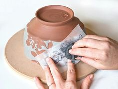Using stencils for slip resist and image transfer to outline the sgrafitto image. Ceramics arts daily
