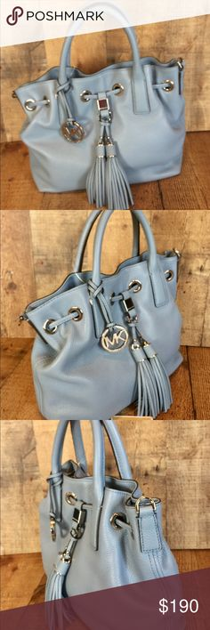 "MICHAEL KORS Camden Med Leather Drawstring Satchel Camden Powder Blue Med. Leather Drawstring Satchel Crafted from luxe leather, the slouchy Camden tote coordinates with every outfit. Soft, pebbled leather beautifully highlights its silhouette, while chic tassels & silver-tone accents. * 		-Soft Venus Leather  * 		-Silver-Tone Hardware  * 		-Top Handle: 4""  * 		-Adjustable Strap: 18""-20""  * 		-11"" W x 9"" H x 4"" D * 		-Interior: One Zip Pocket, Two Open Pockets, One Key Fob  * 		-Magnetic…"