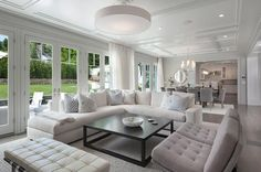 Chic living room features a white linen sectional lined with blue pillows facing a black coffee table and a pair of gray tufted accent chairs placed in front of a wall of French glass doors leading out to the patio.