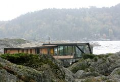 Lille Aroya is a residence nestled in the rocky seaside of Larvik in Norway. Designed by architect Lund Hagem , this villa was originally the holiday home of a Lund, House On Stilts, Kabine, Small Buildings, Residential Architecture, Architecture Design, Inspired Homes, Norway, Exterior