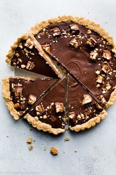 Snickers caramel tart with salted caramel, peanut crust, salty peanuts, and chocolate peanut butter topping! Recipe on sallysbakingaddiction.com