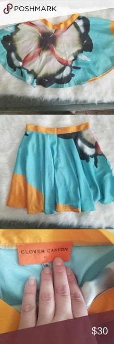 Clover Canyon Circle Skirt Adorable circle skirt from Clover Canyon, large flower on front with main colors of turquoise and yellow. In great condition, save one small irregularity near the zipper in the back, see last photo. Due to the style of the skirt it is not very noticable at all when wearing. Perfect for spring and keeping cool in the summer!! Waist is 14 inches, no stretch. Clover Canyon Skirts Circle & Skater