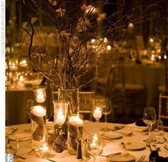 Branches as main center.  Surrounded by candles.  Pinecones.  White table clothes.  Could do some greenery/white as well