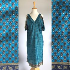 This beautiful blue kaftan dress is made in Cape Town from sari fabric. It was designed to make women feel comfortable while looking elegant. It is a fitted dress that is easy and light having a v-neck design that is perfect for the bust and an additional design of two side slits and a cold shoulder.