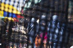 This Thursday, April 11, 2013 photo taken through the eye slit of a burqa, shows Afghan women in Burqa's shopping at a market in Kabul,…