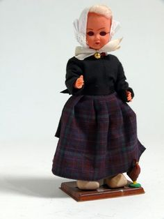 Eine blonde Frau in der Tracht von Kampen, Niederlande. Ein schwarzes, zweiteiliges Kleid mit dunkelblau karrierter Schürze. Weiße Spitzenhaube und rote Perlenkette mit Goldverzierung. Holzschuhe. Neben der Puppe links ein braunes Hühn. #Overijssel #Kampen
