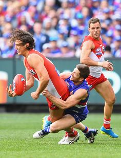 Kurt Tippett of the Swans handballs whilst being tackled by Dale Morris of the Bulldogs during the 2016 AFL Grand Final match between the Sydney...