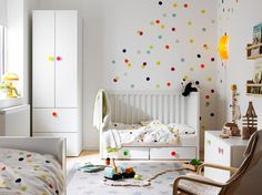 A small children's bedroom furnished with a white cot with floor drawers, converted into a children's bed. Shown together with a white wardrobe and a storage bench with colourful knobs.