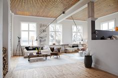 Wood ceiling, white couch. White beam. Reading lamps. Big windows.