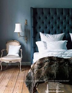 gray cushioned headboard, wooden floors, plush bedding with crisp white sheets, elegant chair... it all works for me!