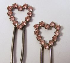 Vintage pair of pink rhinestone heart hair pins •Prong set glass stones •Great for a vintage wedding bride •Silver tone setting •Each heart is