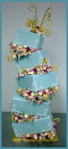 Tiffany blue whimsical wonky cake.  Shades of pink roses and whimsical gold curls. White scroll work at corners.