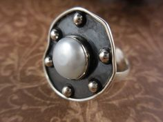 Made with natural 10mm freshwater pearl and antiqued.925 sterling silver metal, accents, and wire. Size 8.5