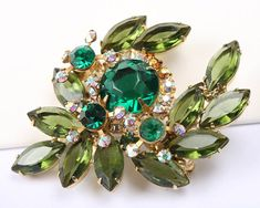1967s Juliana Green Rhinestone Brooch and Earrings Set Product Description Stunning 1960s brooch and earring set featuring green rhinestones. The brooch and earrings both feature different shades of green. The earrings are clip on and all is in excellent condition. This set has