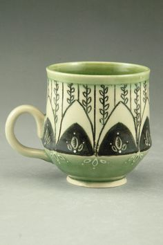 Handmade porcelain mug with black underglaze painting and inlay, sgraffito, and…