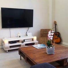 DIY  tv stand made from used pallets. White washed for rustic feel. This tv stand is also made with a step up to create a more dynamic look and feel.  Interior  design.  You will recognize  the coffee table from my previous  pallet furniture  projects. This be refurbished  to match the room. Share your  thoughts  of this too  must be painted white.