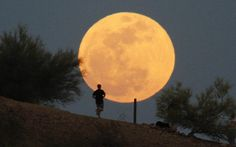 A runner makes his way along a trail on a butte in front of the moon at Papago Park in Phoenix.