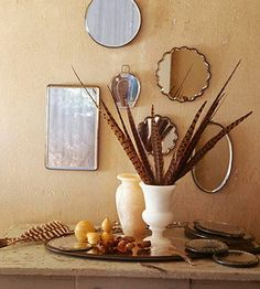 Simplicity Reigns: Dress up a side table for Thanksgiving with a simple arrangement of tall pheasant feathers in a ceramic urn. Surround with small gourds, pinecones, and loose feathers.