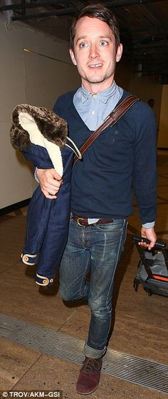 How the Stars DO Airports: The Sundance Kids: Elijah Wood (left) showed off his preppy style in a buttoned-up shirt, cardigan, cuffed jeans and red and brown suede sho...