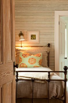"""Think """"little cabin in the woods."""" Whitewashed wood-paneled walls, an iron bed frame and rustic linen bedding."""