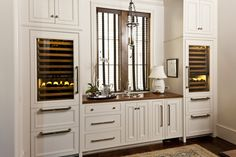 Fantastic butler's pantry boasts white cabinets with raised panel doors topped w… Wood Bar Cabinet, Cabinet Ideas, Wine Fridge, Wine Refrigerator, Wood Countertops, Walnut Countertop, In Vino Veritas, Butler Pantry, Wood Bars