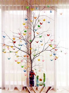 Tree branch with tiny paper cranes hung all over