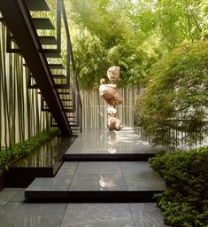 A Nick van Woert sculpture punctuates the garden, which was designed by Rees Roberts + Partners | archdigest.com