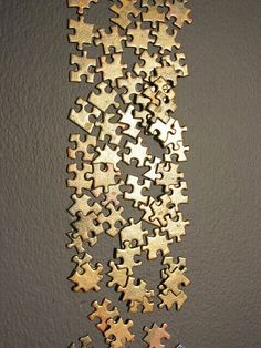 Paint your old puzzle pieces with gold or silver and stick them on the wall!!Looks expensive #GlitterGrout