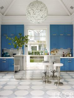 Vintage items meet modern design in a Bridgehampton house designed by Timothy Haynes and Kevin Roberts. The bright blue cabinets and smoked mirror-paneled bar are custom-made and the floors are of honed Thassos and Atlantic Blue marble. The counters are cast glass, the circa-1970s stools are attributed to Karl Springer and the 1960s chandelier is made of Murano glass.