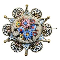 This is an antique Micro Mosaic brooch depicting colourful flowers and ornaments on a white ground. The glass tesserae are tiny and smooth to the