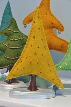 felt Christmas trees -- these would be cute handmade with sticks for trunks and something else natural for the base.  Would be darling for a dollhouse, especially with miniature ornaments (beads).